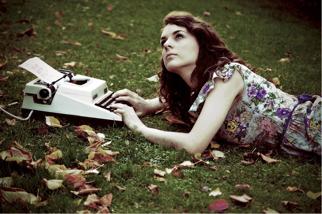 escrevendo com máquina de escrever na grama